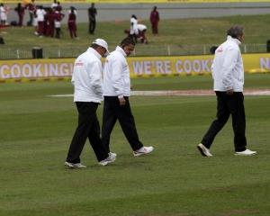 The umpires and ground staff inspect the playing surface on the fourth day of play. Photo: Reuters