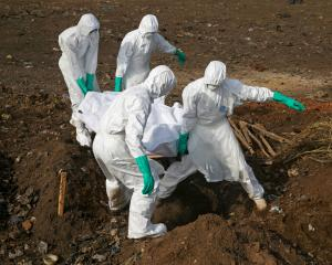 Health workers carry the body of a suspected Ebola victim for burial at a cemetery in Freetown,...