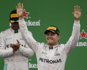 Nico Rosberg celebrates his win on the podium after the race as Lewis Hamilton looks on. Photo:...