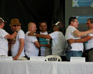 FARC commander Ivan Marquez and members of the leadership congratulate each other after a news...