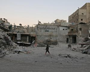 A boy walks amid damaged buildings in the rebel held area of al-Kalaseh neighbourhood of Aleppo....