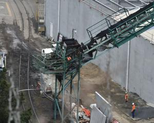 Port Otago staff assess the damage, following a fire on a Port Otago conveyor belt yesterday....