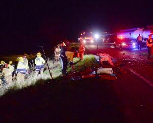 Firefighters work to free a woman from her car after a crash involving two cars and a petrol...