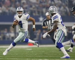 Dallas Cowboys quarterback Dak Prescott (4) scrambles for a first down in the first quarter...
