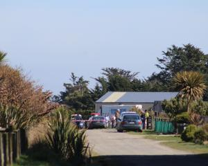 Police officers, a forensic van and other people and vehicles at 129 Otatara Rd, Otatara, near...