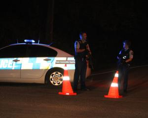 Armed police block a road near the scene of a shooting in Otatara this evening. Photo: Allison...