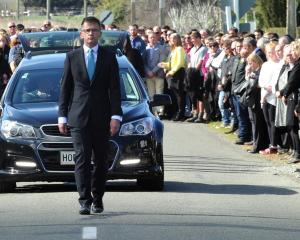 A guard of honour stretches down Horse Range Rd as the family of Andrew Grubb walk behind the...