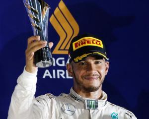 Mercedes' Lewis Hamilton of Britain celebrates on the podium. Photo: Reuters