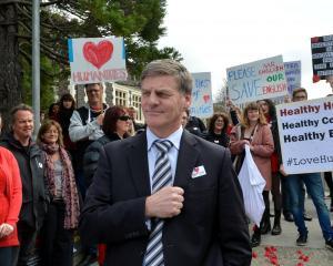 Tertiary Education Union Dunedin organiser Shaun Scott (left, partially obscured) talks to Deputy...