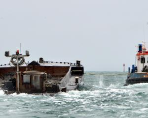 Port Otago' work boat Kapu tows the $1.4million, spoil-laden barge Hapuka out to sea yesterday....