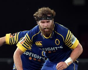 Otago captain Liam Coltman looks for the ball despite being held back by Northland loose forward...