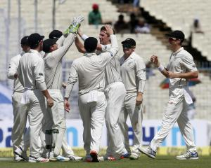 New Zealand's Matt Henry (3rd from right) is congratulated by his teammates after taking the...