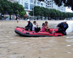 People take a boat at a flooded area as Typhoon Megi lands in Fuzhou, Fujian province, China....
