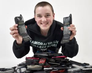 Kaikorai Valley College pupil Nathan Harris with his growing pile of old mobile phones, which he...