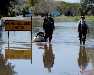 Local residents wade along a road closed due to flooding following heavy rains in the midwestern...