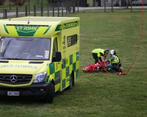 An ambulance officer and paramedic attend to a paraglider injured in a  crash, after he was...
