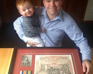 Shawn McAvinue (38) with 7-month-old son Cormac and the service certificate and medals of his...