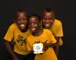 Children hold a solar buddy. Photo supplied