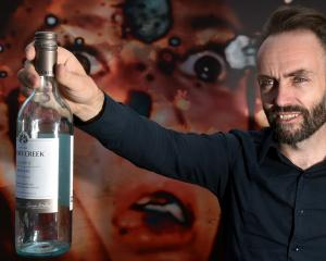 Transmedia artist Simon Wilkinson, of England, offers a bottle outside his virtual reality...
