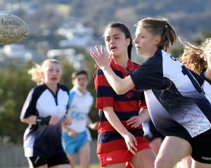South Otago High School player Tia Valli (14) offloads the ball. (from left) Charlotte Power (16)...