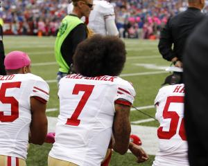 Colin Kaepernick takes a knee before the 49ers game against the Bills. Photo: Reuters