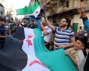 People carry Free Syrian Army flags while attending a protest against evacuating civilians, in...