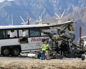 Investigators confer at the scene of the crash on the westbound Interstate 10 freeway near Palm...