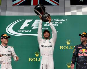 Lewis Hamilton raises the trophy watched by Nico Rosberg (L) and Daniel Ricciardo. Photo Reuters