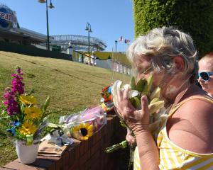 People leave floral tributes to the accident victims outside the main entrance to Dreamworld....