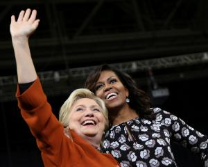 Hillary Clinton (L) arrives at a campaign rally in Winston-Salem, North Carolina, accompanied by...