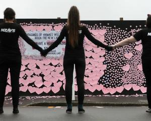 Animal rights activists contemplate the cardboard hearts on the building site of the animal...