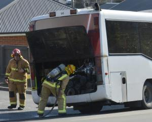 A fire-fighter checks the engine bay of the bus after the fire was extinguished. Photo: Gerard O...