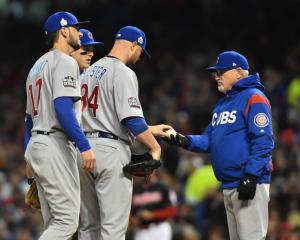 Chicago Cubs manager Joe Maddon (right) takes the ball from starting pitcher Jon Lester (34) in...