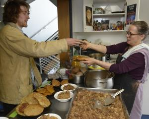Student Max Gunn receives a plateful of vegetarian goodness from Hare Krishna Jane Beecroft, who...