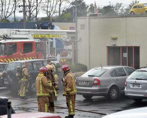 Firefighters assess the fire-damaged office of IDEA Services. Photo by Peter McIntosh.