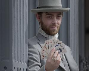 Actor Tom Clarke, as Mr Pilgrim,  splays playing cards in Dunedin yesterday featuring characters...