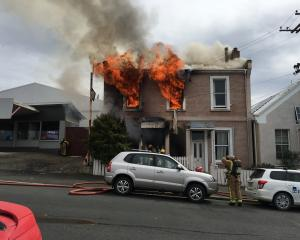 Firefighters enter a Dunedin flat that was ''totally destroyed'' in a fire yesterday. Photos:...