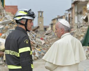 Pope Francis talks with a firefighter in front of a building that collapsed after the August...