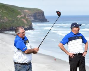 Otago masters No1 Andrew Hobbs plays a shot, watched by manager Chris Timms, at the ninth hole at...