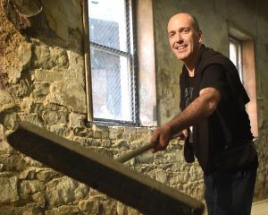Arts Festival Dunedin director Nicholas McBryde sweeps the floor of the Athenaeum basement...