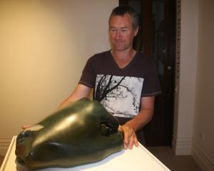 Luggate artist Joshua Olley adjusts one of his pieces at the Forrester Gallery. Photo: Shannon...