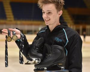 Reuben Dougherty displays his gold medals from the national figure skating champs last week....