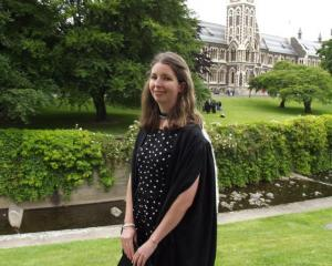 Brittany Travers outside the University of Otago clocktower building in her graduation gown....
