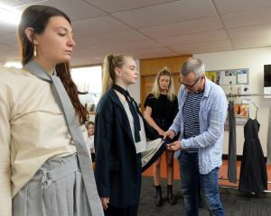 Void owner Neil Gaudin inspects designs modelled by Frank  Jansen van Rensburg (left) and...