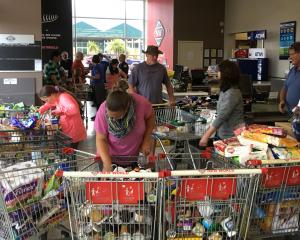 With aisles roped off, shoppers rummage for supplies from the jumble of shopping trolleys at...