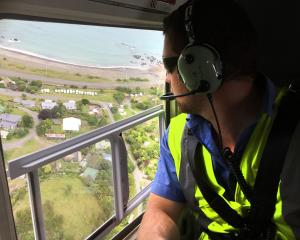 Jordan Hopcroft, of Garden City Helicopters, checks for inhabitants in need of help at Goose Bay,...