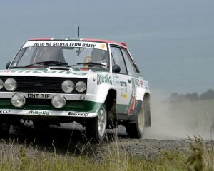 Matthew Robinson and Sam Collins lift a wheel of their Fiat 131 during stage 20 of the Silver...