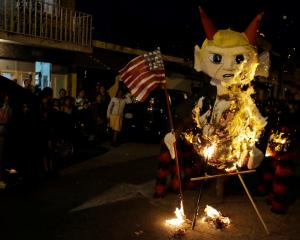 A pinata representing US President-elect Donald Trump as a devil burns during the traditional...