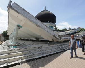 People walk near a collapsed mosque following an earthquake in Meuredu, Pidie Jaya. Photo: Reuters