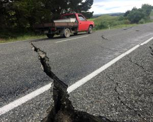 A truck drives over the fractured road caused by an earthquake south of the town of Ward. REUTERS...